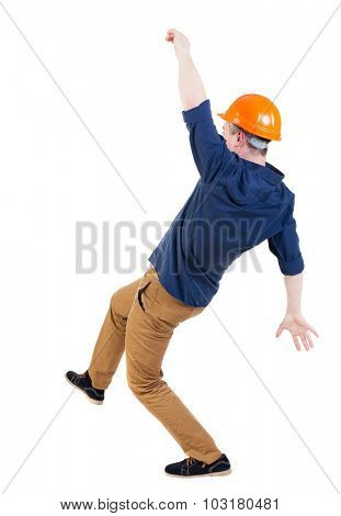 Balancing young man.  or dodge the falling man. worker in construction helmet falls. Rear view people collection.  backside view of person.  Isolated over white background.