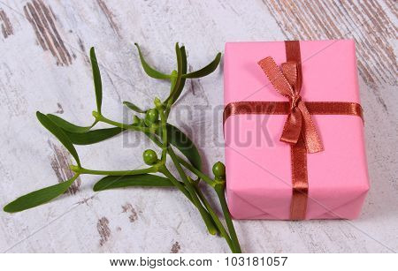 Wrapped Pink Gift For Christmas And Mistletoe On Old Wooden Background