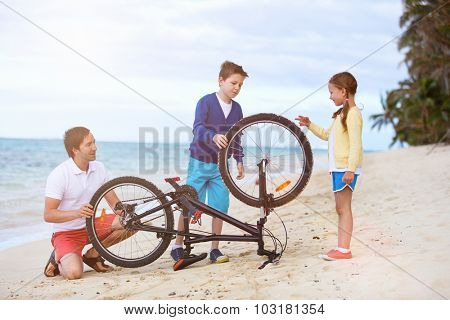 Family of teenage boy, little girl and father repairing bicycle outdoors on tropical beach at summer