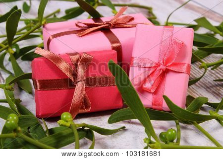 Wrapped Gifts For Christmas And Mistletoe On Old Wooden Background