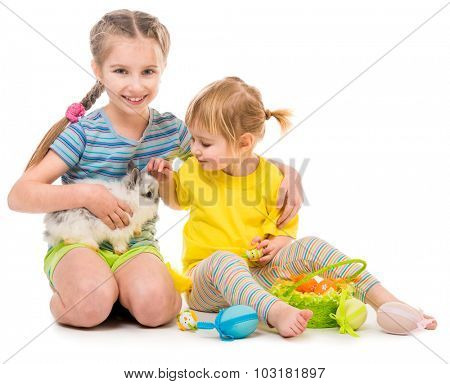 Easter photo. happy little sisters with her rabbit. Isolated on white background