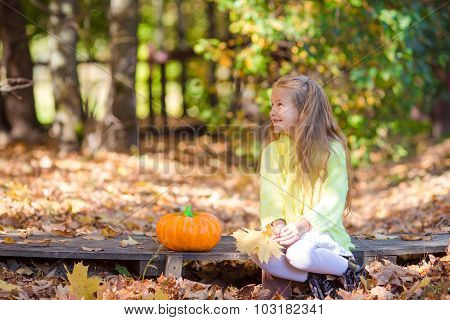 Adorable little girl with a pumpkin for Halloween outdoors at beautiful autumn day