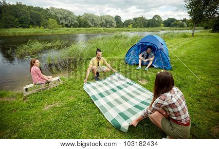 camping, travel, tourism, hike and people concept - happy friends with tent laying picnic blanket at campsite on river bank
