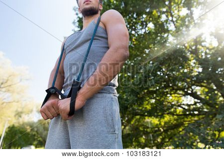 fitness, sport, exercising, training and lifestyle concept - close up of young man exercising with expander in summer park