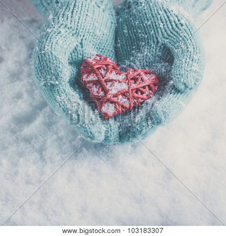Female hands in light teal knitted mittens with entwined red heart on a white snow background. Love and St. Valentines Day concept.