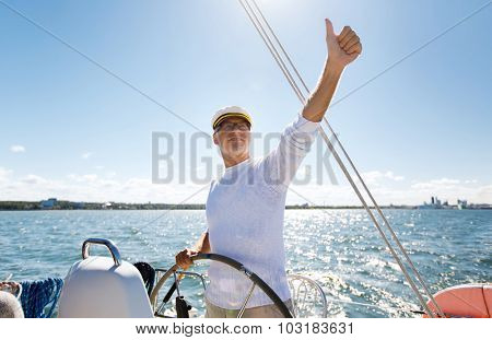 sailing, age, tourism, travel and people concept - happy senior man in captain hat on steering wheel and showing thumbs up sail boat or yacht floating in sea