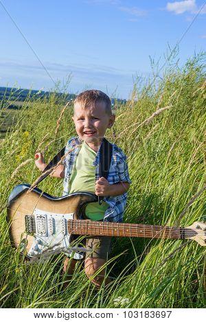 Little Boy With A Guitar On A Walk