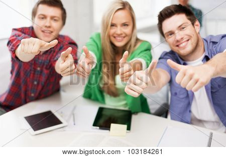 education, people, friendship and learning concept - close up of happy high school students or classmates showing thumbs up