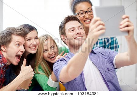 education, people, friendship, technology and learning concept - group of happy international high school students with tablet pc computer taking selfie in classroom and showing thumbs up