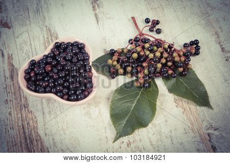 Vintage Photo, Fresh Elderberry With Leaf In Glass Dish On Old Wooden Background