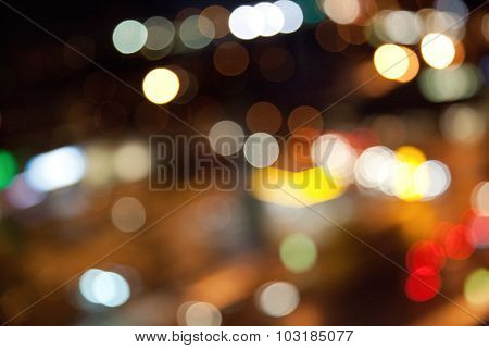 holidays, illumination and electricity concept - colorful bright bokeh lights on dark night background