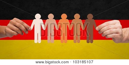 community, unity, population, race and humanity concept - multiracial couple hands holding chain of paper people pictogram over german flag background