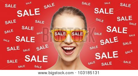 people, summer, shopping and sale concept - happy screaming teenage girl in shades over red background with sale signs