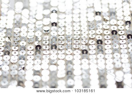 sewing, texture, background, design and embroidery concept - close up of silver sequined textile texture