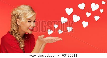 people, holidays, valentines day and love concept - lovely woman in red clothes sending heart shapes from on palms of her hands over red background