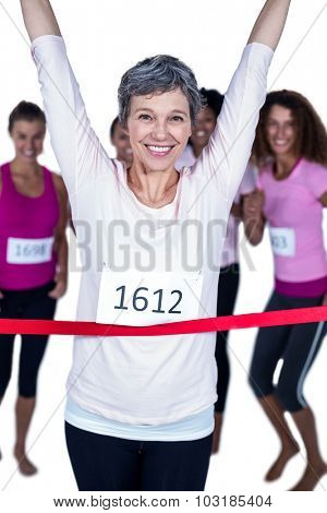 Portrait of happy winner athlete crossing finish line with arms raised against white background