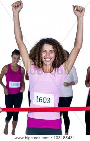 Portrait of smiling winner female athlete crossing finish line with arms raised against white background
