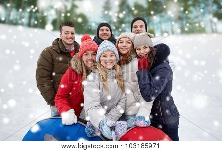 winter, leisure, friendship, technology and people concept - group of smiling young men and women with snow tubes taking picture with smartphone selfie stick outdoors