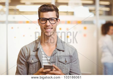 Portrait of handsome businessman texting on phone with colleague working in background at office