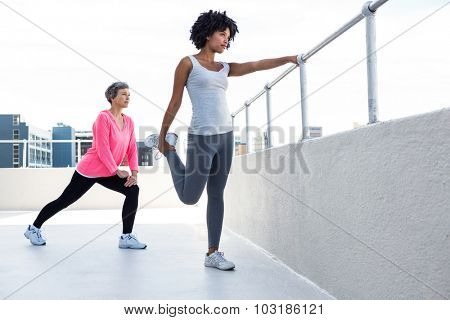 Woman exercising with female friend by railing outdoors