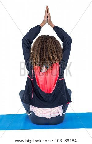 Rear view of woman in yoga position sitting on exercise mat against white background