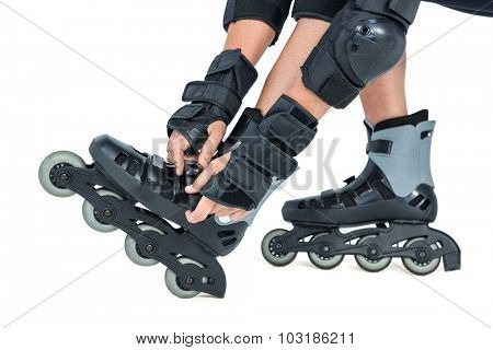 Low section of woman wearing inline skates against white background