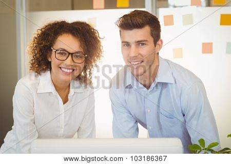 Portrait of business people standing by table in office