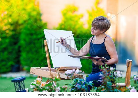 Happy woman painting a picture on an easel on a warm day