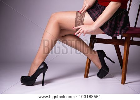 Slender Girl Putting On Stockings