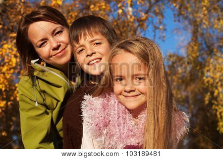 Autumn family portrait in the sunny forest - focus on little girl