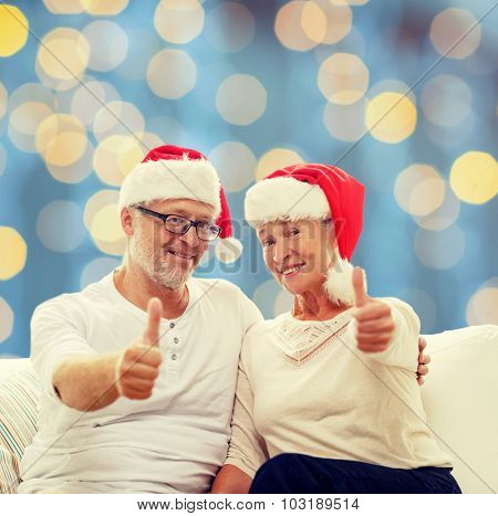 family, holidays, christmas, age and people concept - happy senior couple in santa helper hats sitting on sofa and showing thumbs up gesture over blue lights background