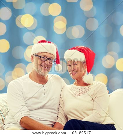 family, holidays, christmas, age and people concept - happy senior couple in santa helper hats sitting on sofa over blue lights background