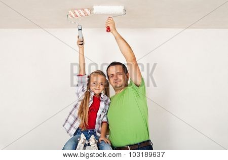 Teamwork - proud father and daughter painting the room ceiling together