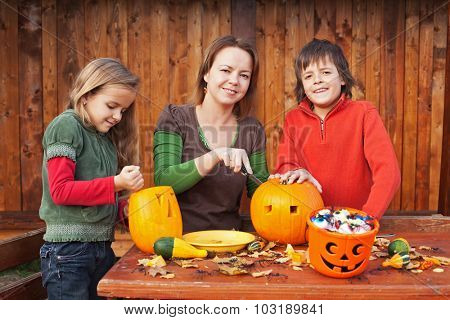 Family carving pumpkin lanterns for halloween - preparing the spooky accessories