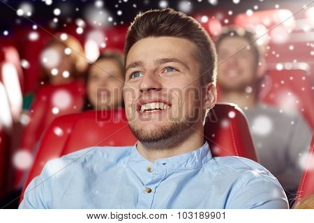 cinema, entertainment and people concept - happy young man watching comedy movie in theater with snowflakes