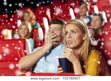 cinema, entertainment and people concept - terrified couple drinking soda and watching horror, drama or thriller movie in theater with snowflakes