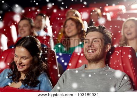 cinema, entertainment and people concept - happy friends watching comedy movie in theater with snowflakes