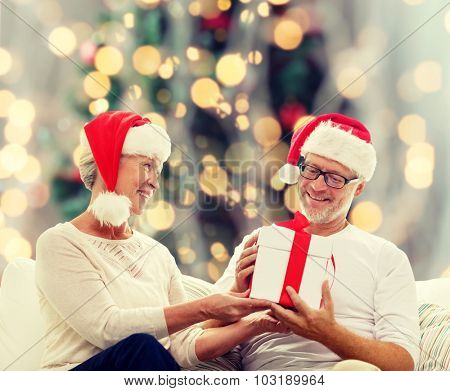 family, holidays, christmas, age and people concept - happy senior couple in santa helper hats with gift box over tree lights background