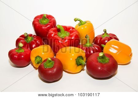 Many Ripe Red And Yellow Peppers On Over White