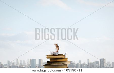 Young lady with laptop on knees sitting on pile of books