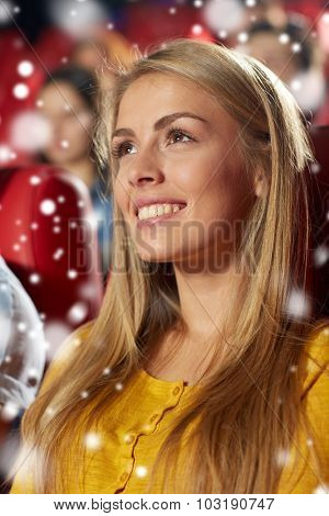 cinema, entertainment and people concept - happy young woman watching comedy movie in theater with snowflakes