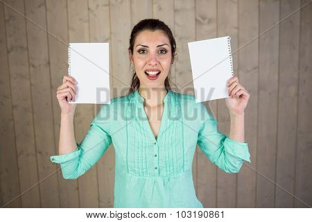 Portrait of woman making face and holding papers while standing against wall