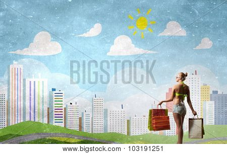Rear view of young pretty woman in bikini and shorts with shopping bags