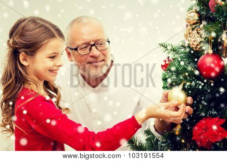 family, holidays, generation and people concept - smiling girl with grandfather decorating christmas tree at home