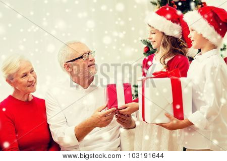 family, holidays, generation, christmas and people concept - smiling family with gift boxes at home