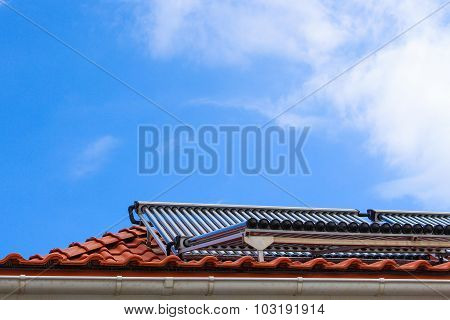 Solar collectors for hot water and heating on the roof of house on blue sky background