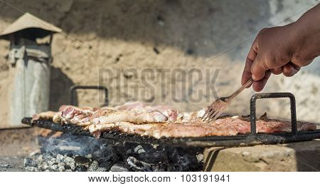 Arranging meat on improvised barbecue