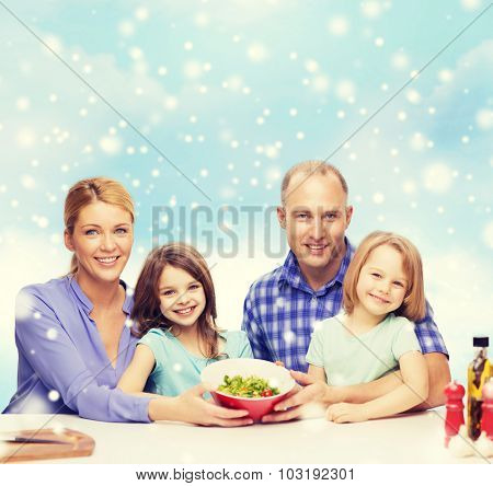 food, family, children, happiness and people concept - happy family with two kids showing salad in bowl over blue sky and snowflakes background