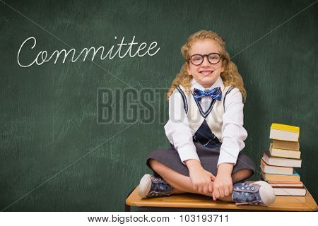 The word committee and cute pupil sitting on table against green chalkboard