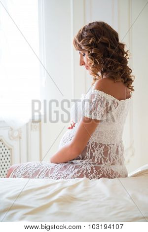 Tender Pregnant Woman Sitting On Bed And Hugging Tummy